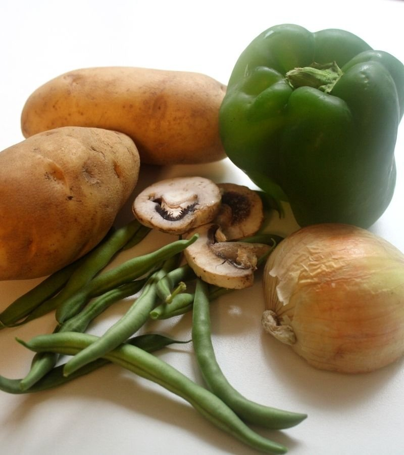 Image of 2 potatoes, one green bell pepper, 1/2 of a yellow onion, fresh picked green beans, and mushrooms with a white background   Mama on the Homestead