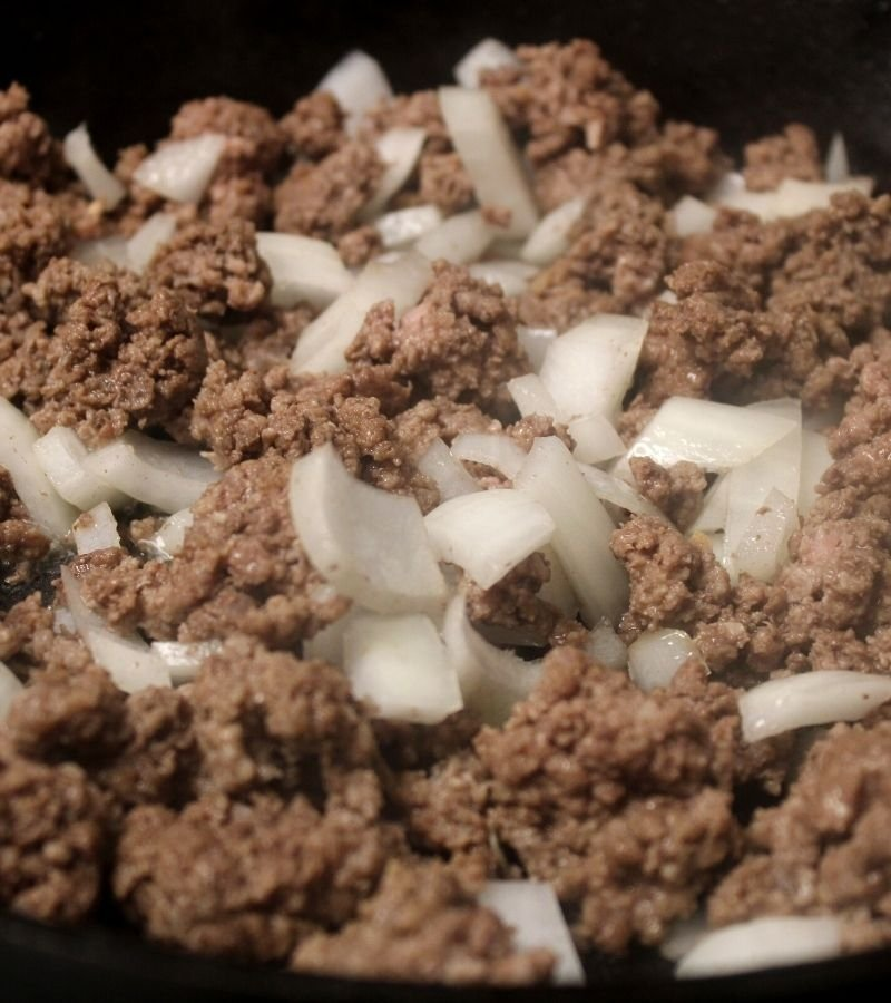 Image of ground beef and onions cooking in a cast iron skillet   Mama on the Homestead