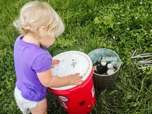 Little girl looking at  DIY Bucket Compost Bin | Mama on the Homestead