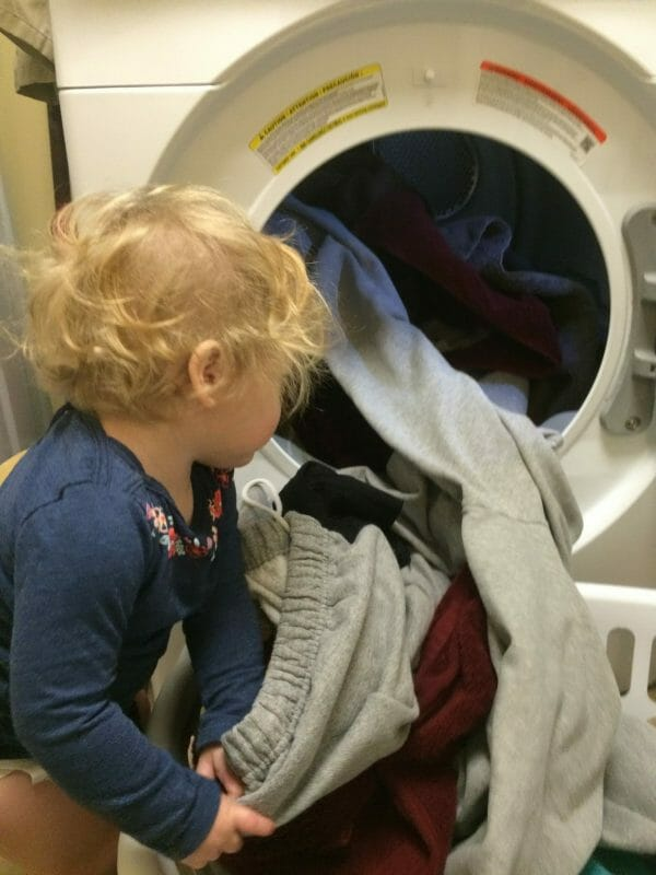 Little girl helping with laundry | 9 Simple Tips for Implementing Farm Chores for Kids | Faithful Farmwife