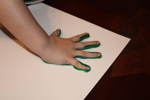 painted hand on paper for handprint shamrock