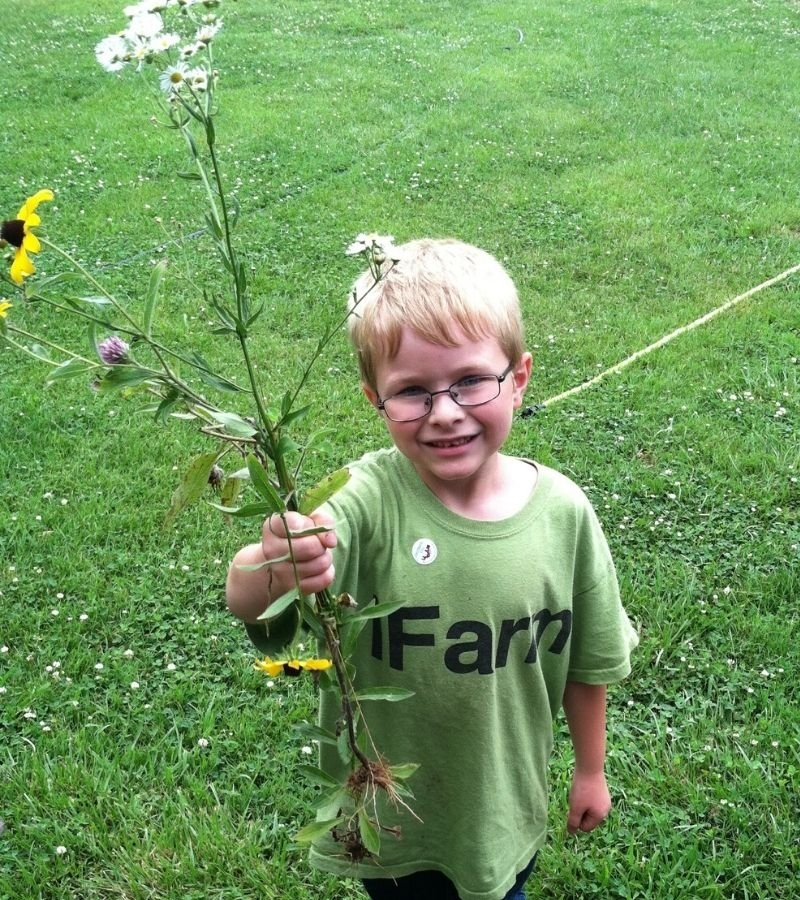 Image of a boy handing wild flowers to his homestead mom | Mama on the Homestead