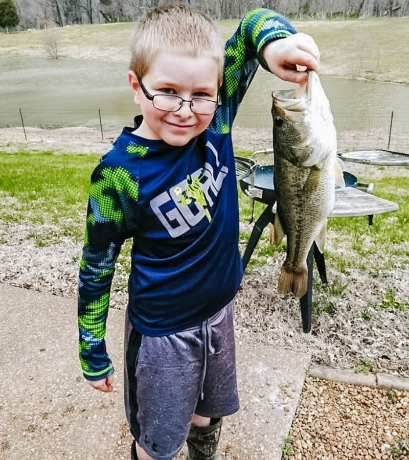 Young boy holding a bass in front of a pond | 30+ Basic Homestead Skills You Need to Learn | Mama on the Homestead