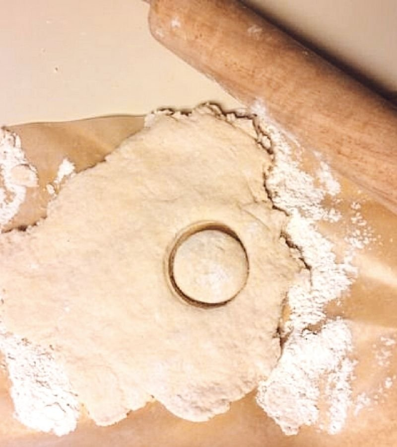 Biscuit dough rolled out on parchment paper with one circle cut out | 30+ Basic Homestead Skills You Need to Learn | Mama on the Homestead