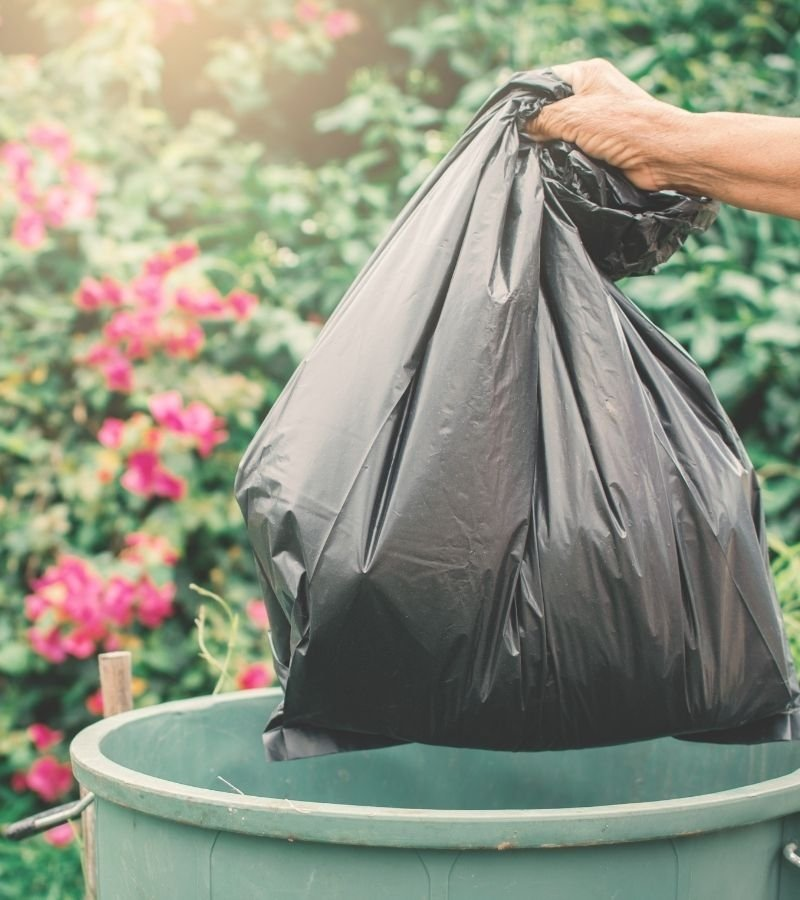 A person placing a large trash bah into a green trash can. Flowers in the background