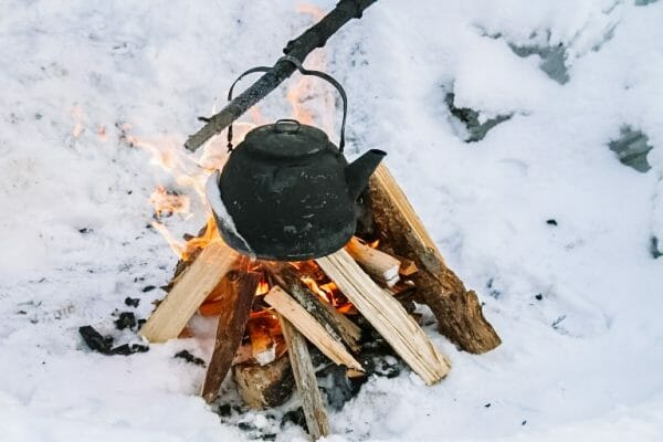 Cast Iron Kettle Over Fire | 20+ Winter Homestead Essentials You Need to Stock | Faithful Farmwife