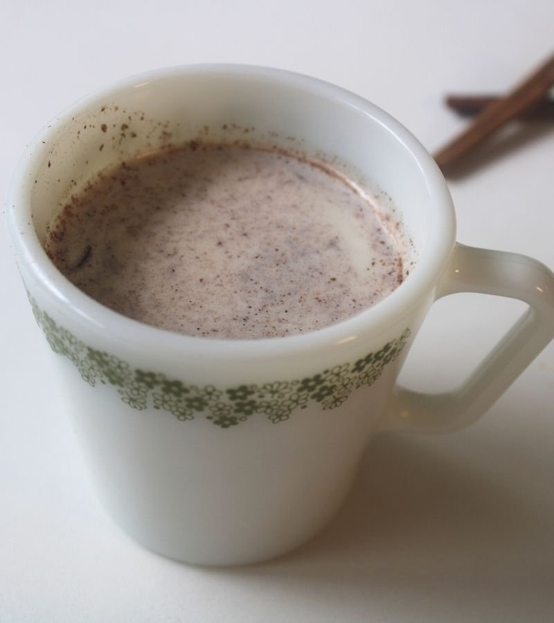 Image of creamy cinnamon sore throat tea in a white tea cup with cinnamon sticks in the background   Mama on the Homestead