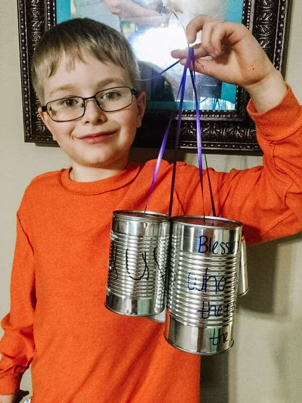 Boy hold 3 tin cans attached to purple ribbon. The cans have Bible verses on them. | 6 Special Christian Easter Activities for Families