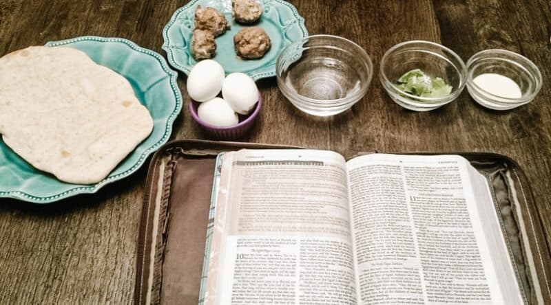 Image of an open Bible and a passover Seder meal- bread, meat, eggs, water, greens | 6 Special Christian Easter Activities for Families