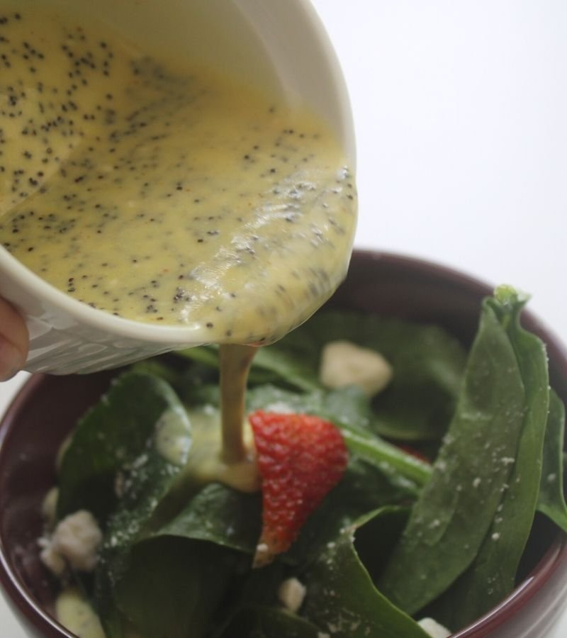 Homemade poppyseed dressing being poured from a white ramekin into a spinach & strawberry salad | Mama on the Homestead