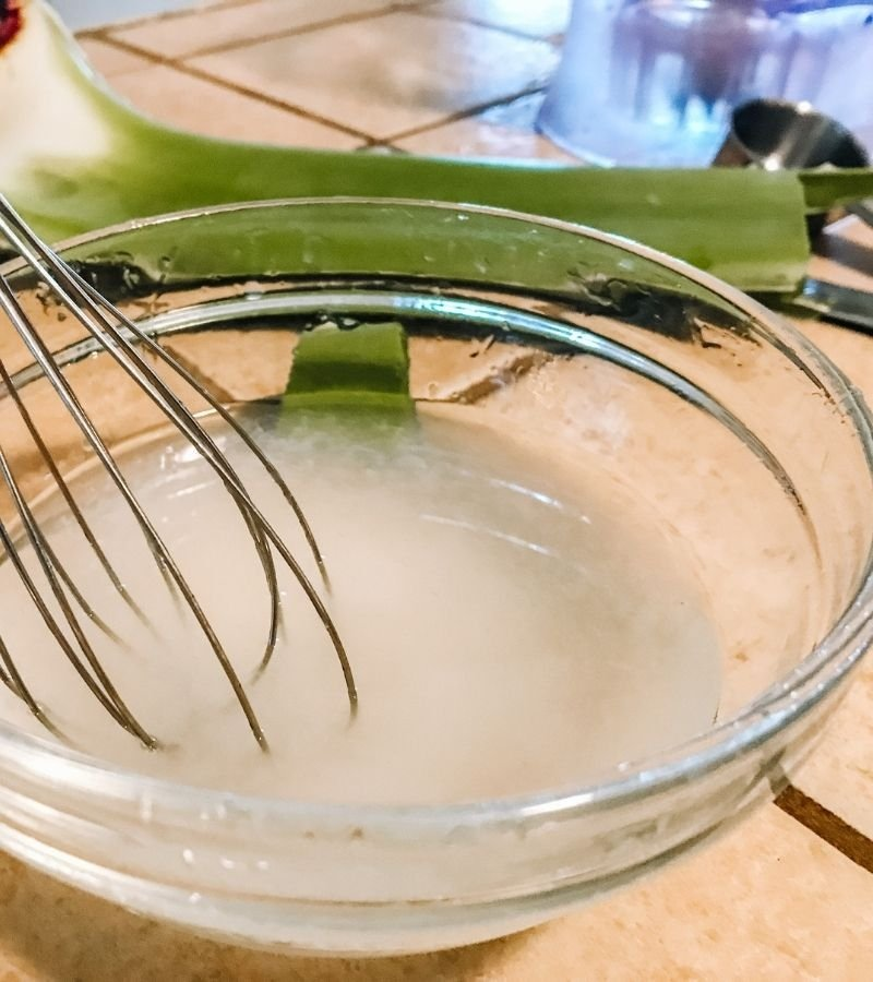 Image of a glass mixing bowl with aloe vera gel and other ingredients being mixed with a whisk.