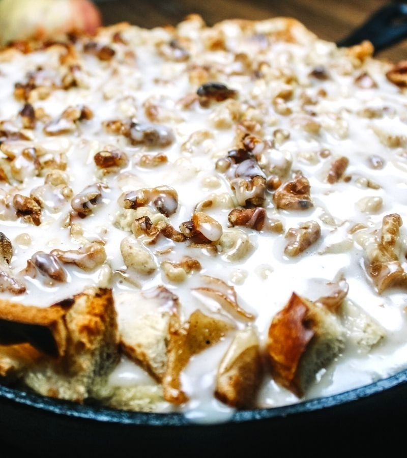 Baked and glazed apple bread pudding in a cast iron skillet