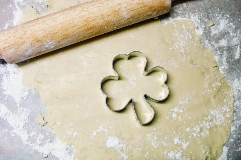 Rolled sugar cookie dough on wax paper with a wooden rolling pin and a shamrock cookie cutter
