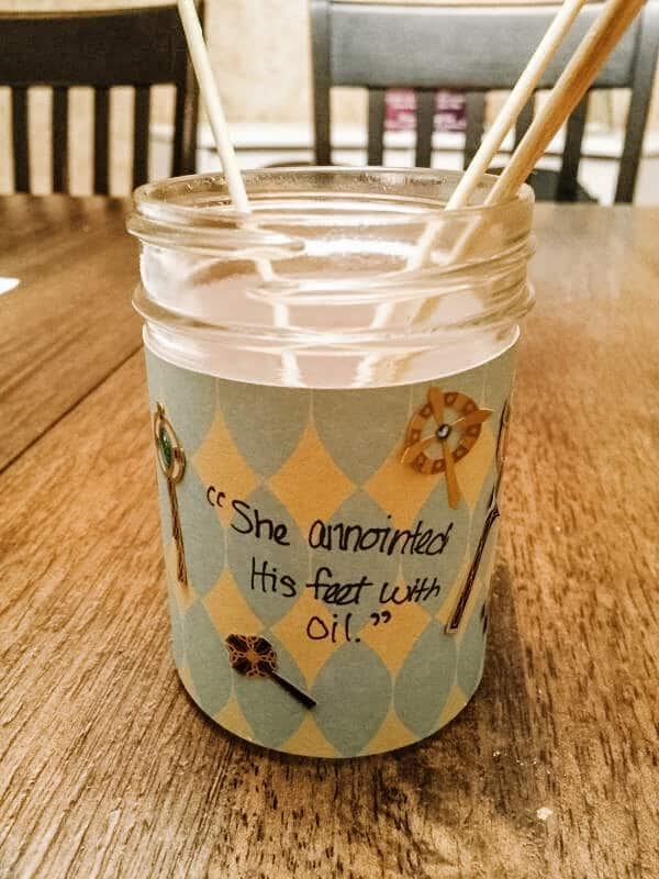 """Small glass jar with essential oil and wooden skewers with the words """"She anointed His feet with oil"""" 