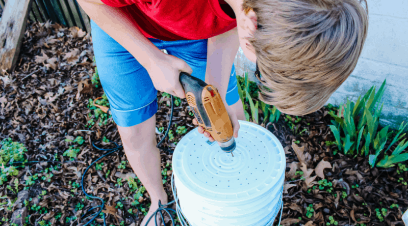Boy drilling holes in a bucket for a worm compost bin | 9 of the Best Gardening Projects for Kids