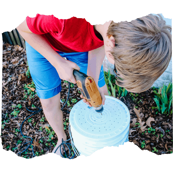 Boy drilling holes in a bucket for a worm compost bin