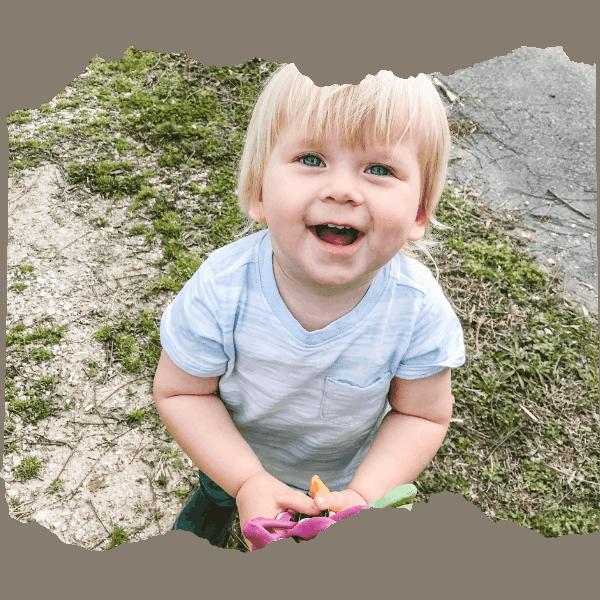 Little boy smiling and holding garden gloves