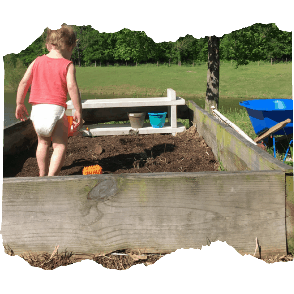 Image of little girl walking in a raised garden bed. Tips for Gardening with Kids | Mama on the Homestead