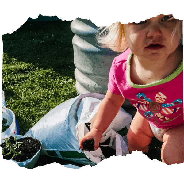 Toddler moving soil into a DIY planting container | 9 of the Best Gardening Projects for Kids