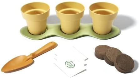Three yellow seed starting pots on a green tray. There is an orange trowel, three seed packs, and three soil discs in front.