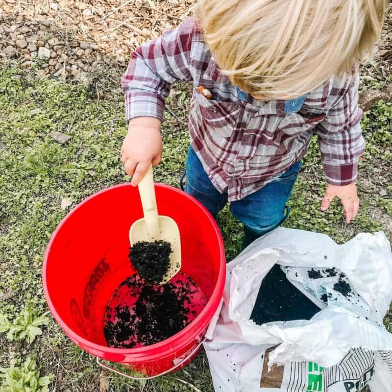 boy scooping soil into a red bucket using a yellow trowel | Kids Garden Tools