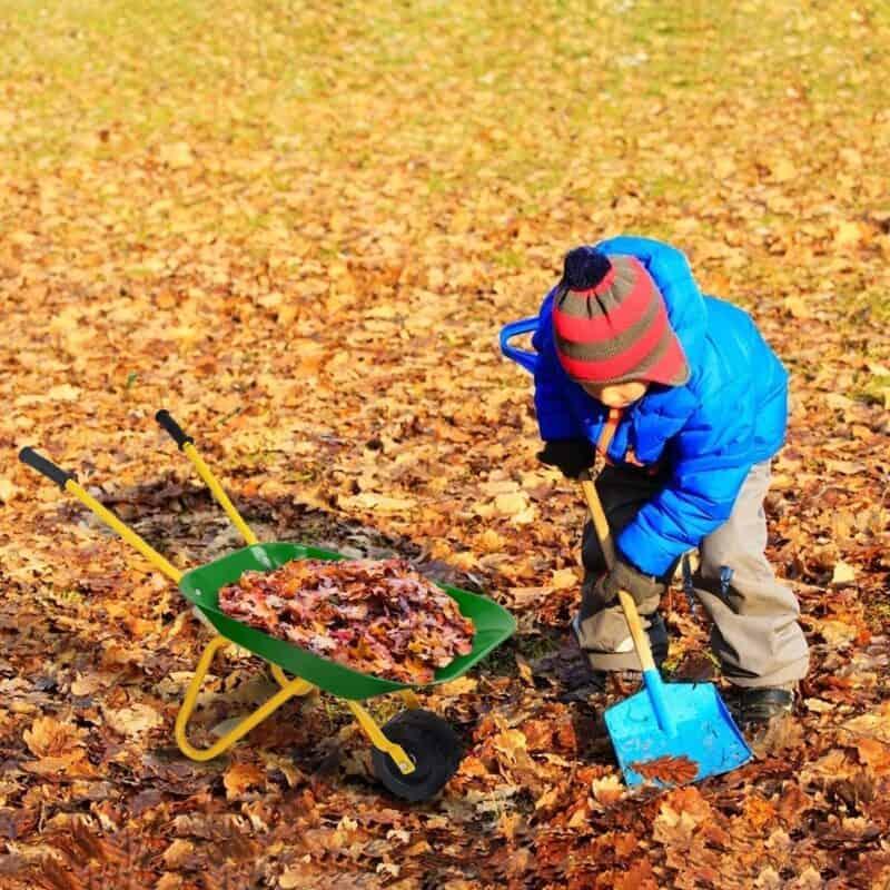 boy shoveling leaves into a green wheelbarrow | Kids Garden Tools