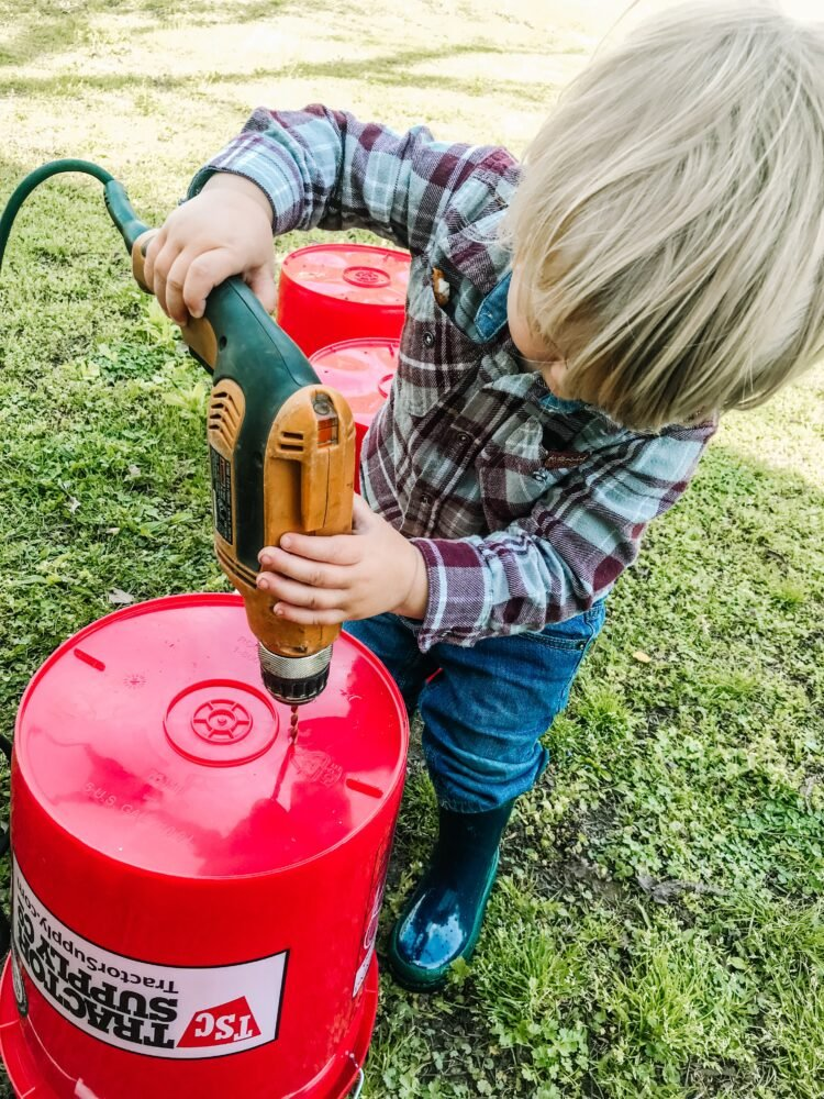 Toddler drilling holes in a 5-gallon bucket