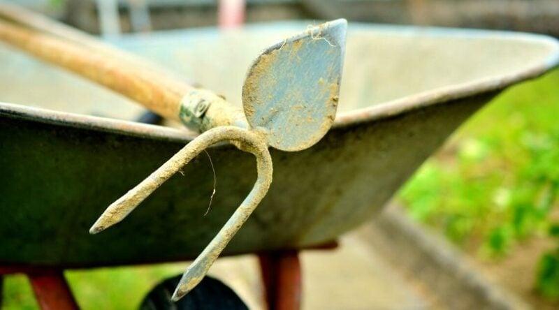 Image of a wheelbarrow with a garden tool