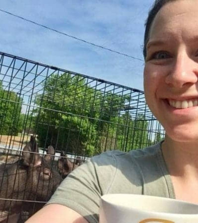Girl sitting in bed of truck with pigs that are in a crate | Mama on the Homestead
