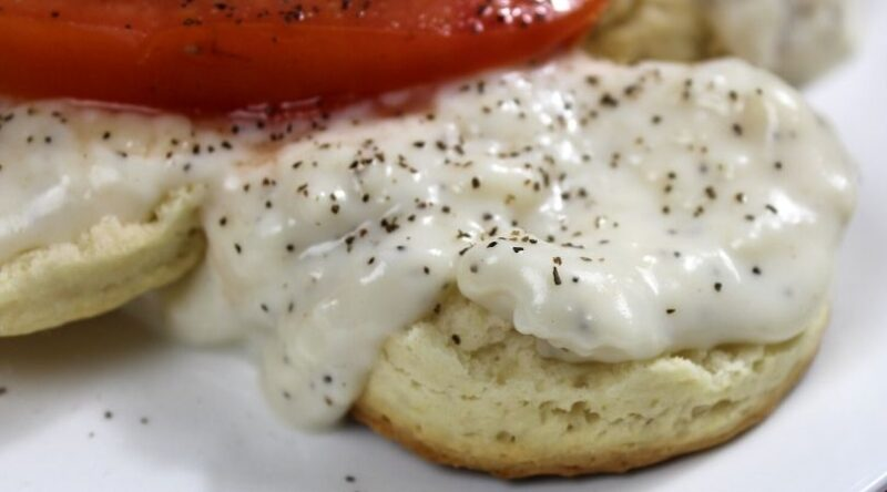 Homemade Biscuits covered with Homemade White Pepper Gravy and a tomato slice | Mama on the Homestead