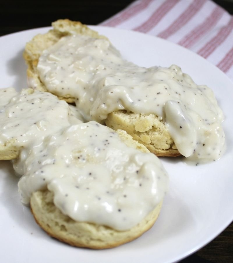 Homemade Biscuits covered in country gravy on a white plate | Mama on the Homestead